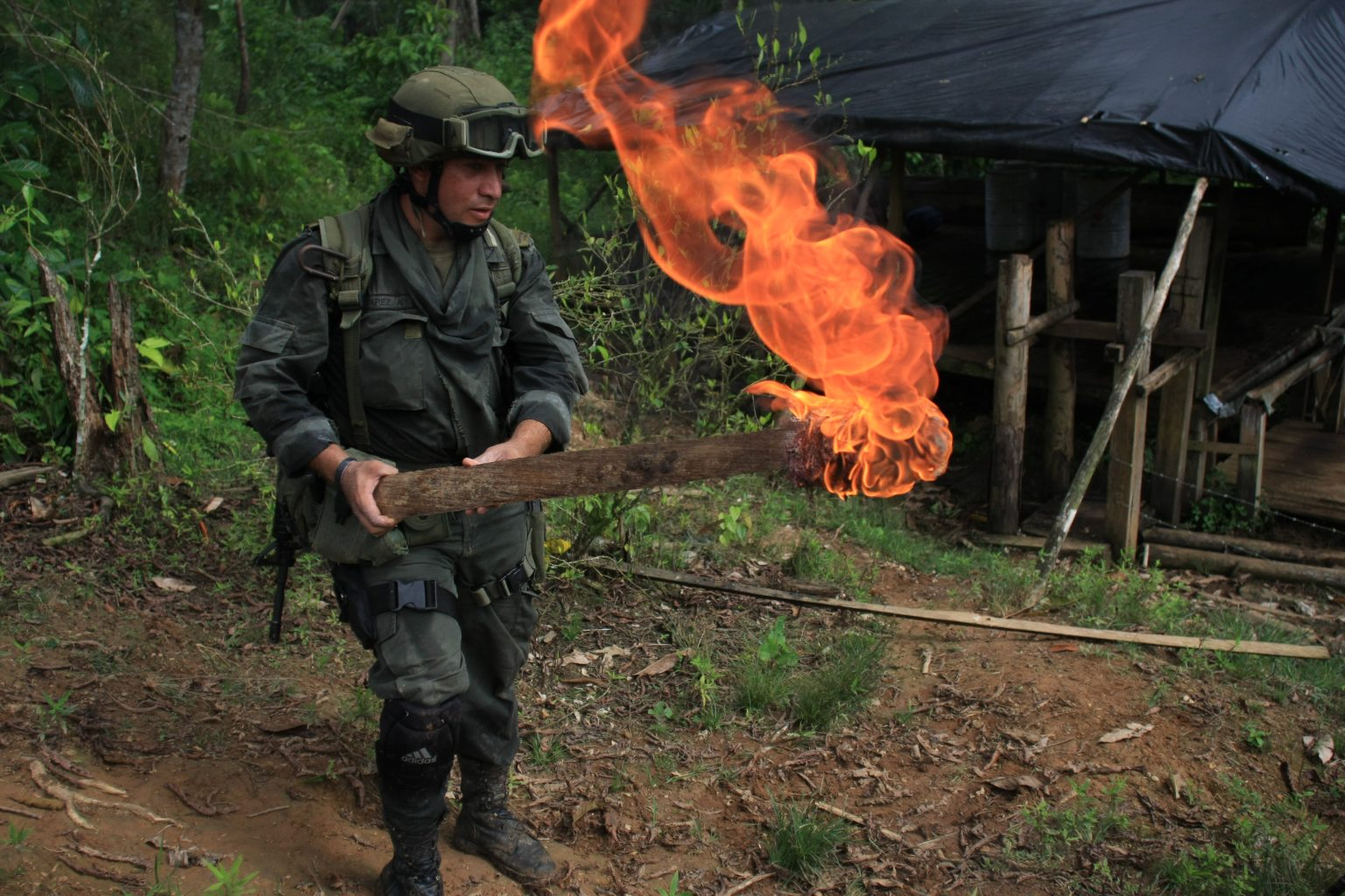 Anti-narcotics police stand on guard after burning a coca laboratory near Tumaco, Colombia. (AP Photo/William Fernando Martinez)